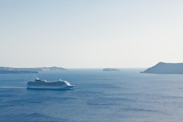 Eine landschaft mit meerblick. kreuzfahrtschiff in dem meer nahe der insel santorini, griechenland