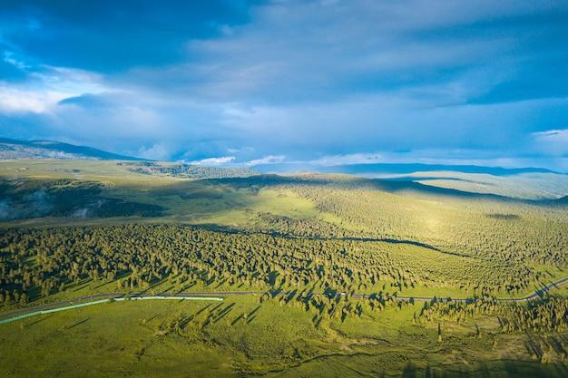 Eine landschaftsansicht des schönen frischen grünen waldes, der straße chui-fläche und des altai-gebirgshintergrundes. panoramablick des schönen grünen waldes in den altai-bergen