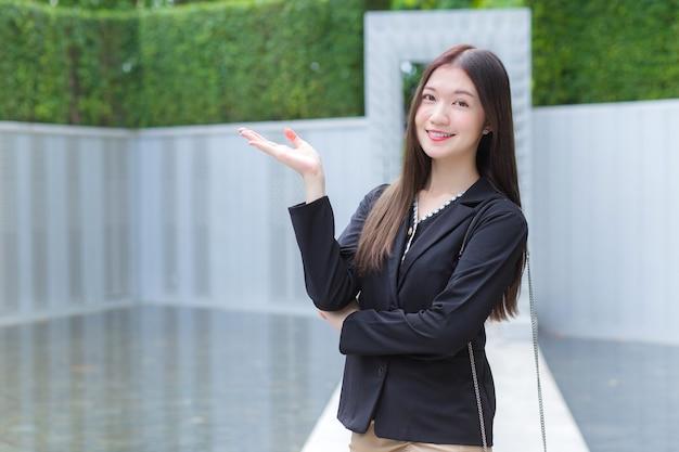 Eine langhaarige asiatische geschäftsfrau im schwarzen anzug lächelt glücklich, als sie etwas präsentiert.