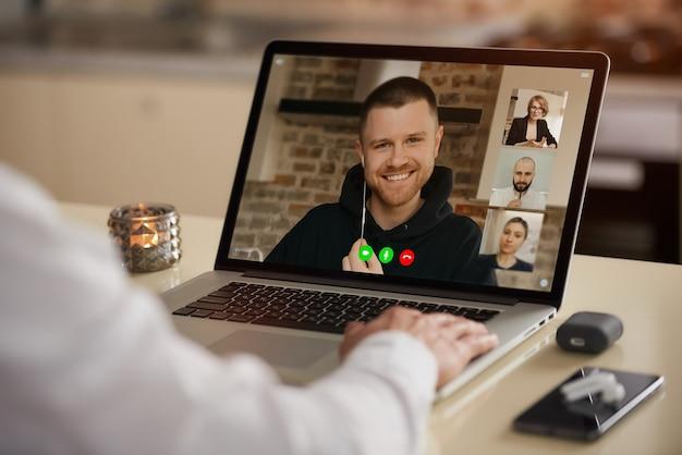 Eine laptop-bildschirmansicht der telekommunikationsanwendung während eines online-meetings über die schulter eines mannes.