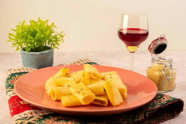 Eine leckere mahlzeit mit italienischer pasta von vorne in der rosa platte zusammen mit rohen pasta und einem glas wein auf buntem teppich und rosa