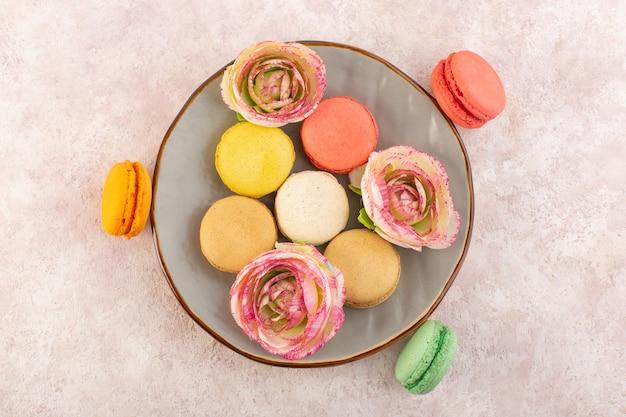 Eine leckere und runde innenplatte der französischen macarons von oben auf dem süßen zucker des rosa tischkekskuchens
