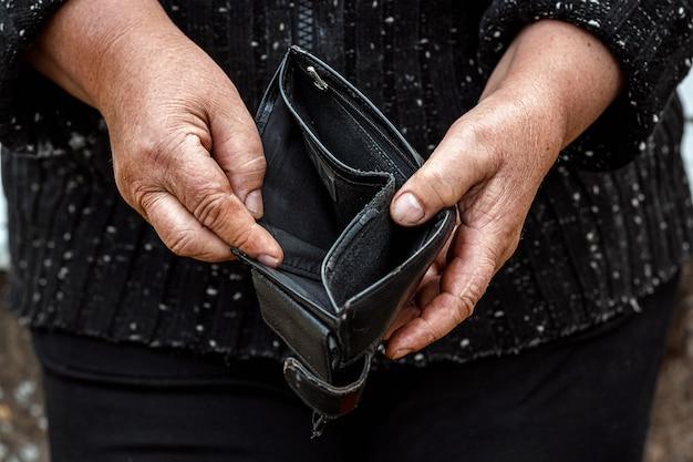 Eine leere brieftasche in den händen eines rentners.