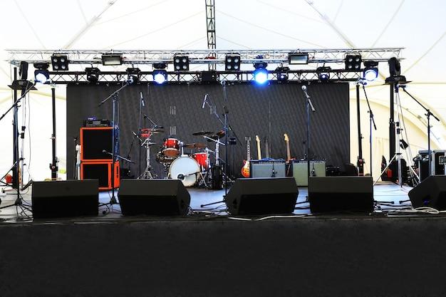 Eine leere bühne vor dem konzert mit flutlicht und musikinstrumenten