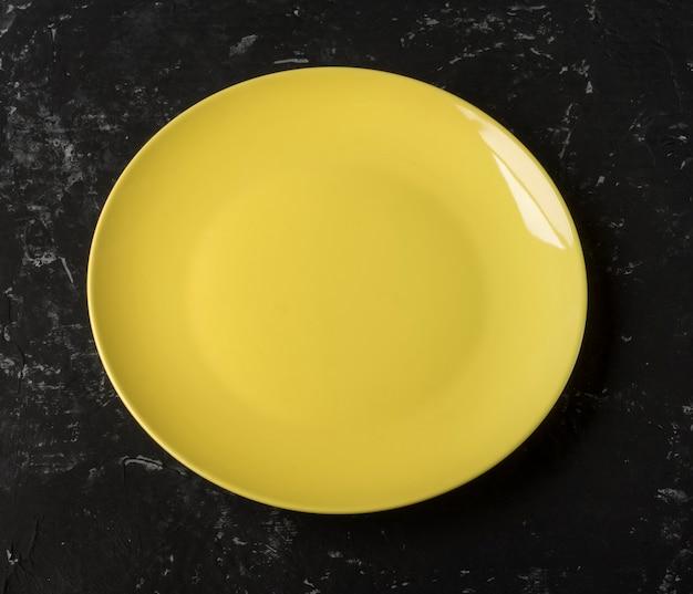 Eine leere gelbe platte auf einem schwarzen strukturierten hintergrund.