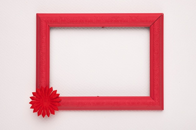 Eine leere hölzerne rote grenze mit blume auf weißer wand