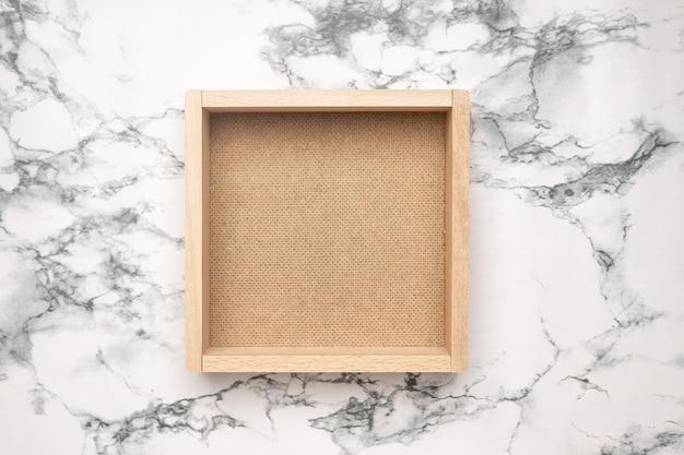 Eine leere holzkiste lokalisiert auf marmorhintergrund-draufsicht