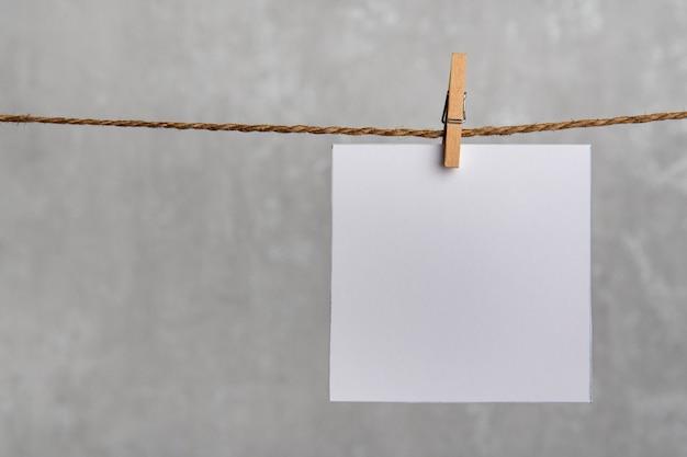 Eine leere quadratische notizpapierkarte, die mit holzclip auf seilschnur hängt