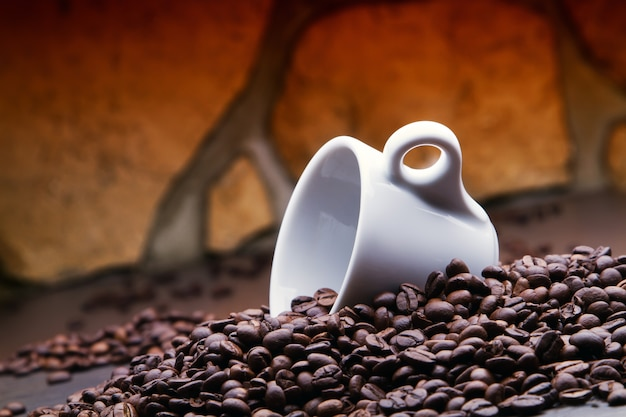 Eine leere tasse zwischen kaffeebohnen.