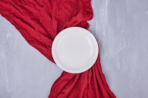 Eine leere weiße keramikplatte auf der tischdecke.