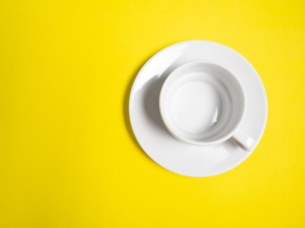 Eine leere weiße tasse und untertasse auf gelbem hintergrund, eine kopie des raumes