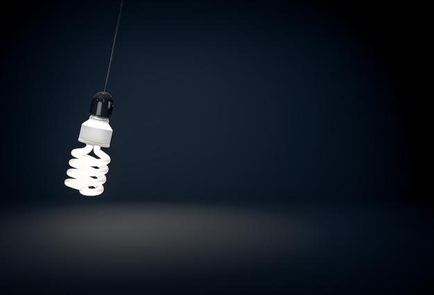 Eine leuchtende öko-energiesparlampe, die in einem dunklen raum am draht hängt