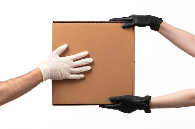 Eine lieferbox mit vorderansicht wird von frau zu mann geliefert, beide in handschuhen auf weiß