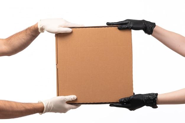 Eine lieferbox mit vorderansicht wird von frau zu mann getragen, beide in handschuhen auf weiß