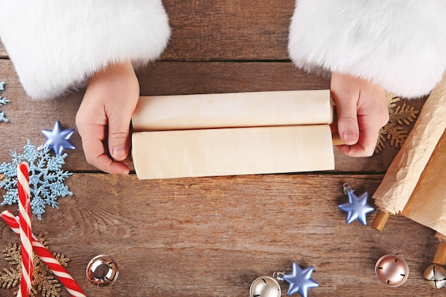 Eine liste von weihnachtswünschen in santa claus händen auf holztisch on