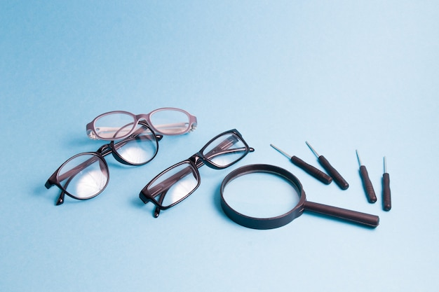 Eine lupe, mehrere brillen und kleine schraubendreher befinden sich auf einer blauen oberfläche