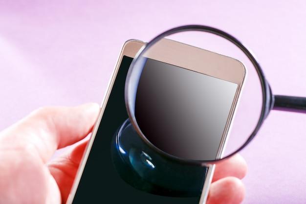 Eine lupe sucht im internet. mann hält smartphone und suchinformationen. attrappe, lehrmodell, simulation.