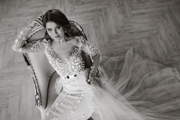 Eine luxuriöse braut in einem hochzeitskleid am morgen in ihrem interieur