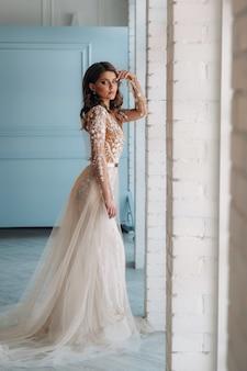 Eine luxuriöse braut in einem hochzeitskleid morgens in ihrem interieur.