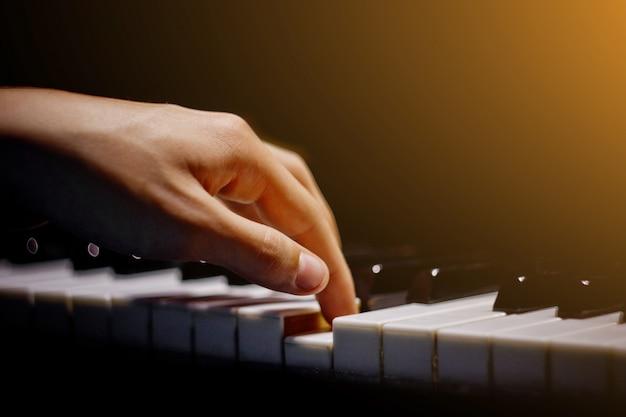 Eine männliche hand am klavier.