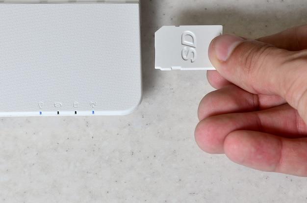 Eine männliche hand fügt eine weiße kompakte sd-karte in den entsprechenden eingang ein