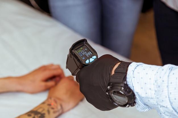Eine männliche hand in einem schwarzen handschuh misst die temperatur am arm des patienten.