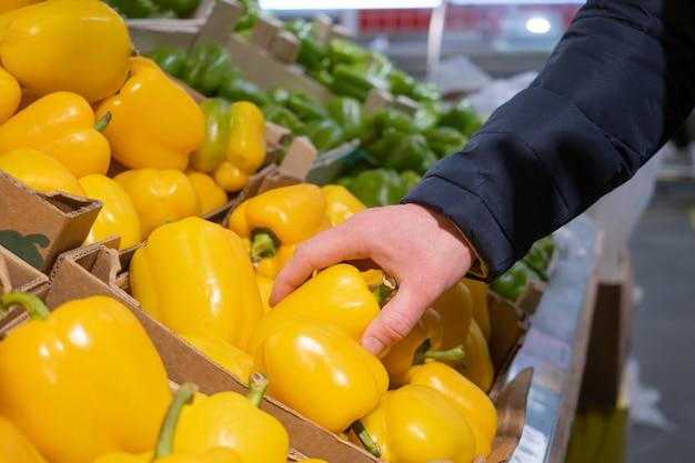 Eine männliche hand nimmt einen gelben pfeffer aus einer schachtel paprika in einem supermarkt.