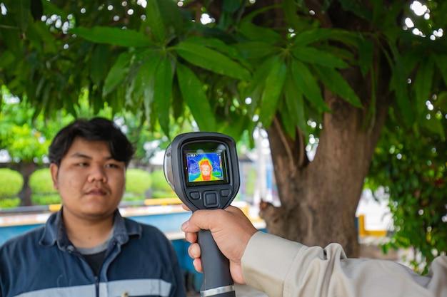 Eine männliche person, die gemessen wird, scannt die körpertemperatur mit einem kontaktlosen infrarot