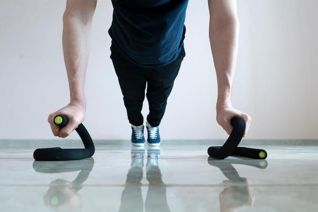 Eine männliche person, die liegestütze auf dem boden macht, den körper fit macht, gesund trainiert