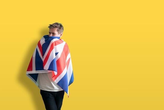 Eine männliche person mit einem patriotismus- und freiheitskonzept der britischen nationalflagge im freien