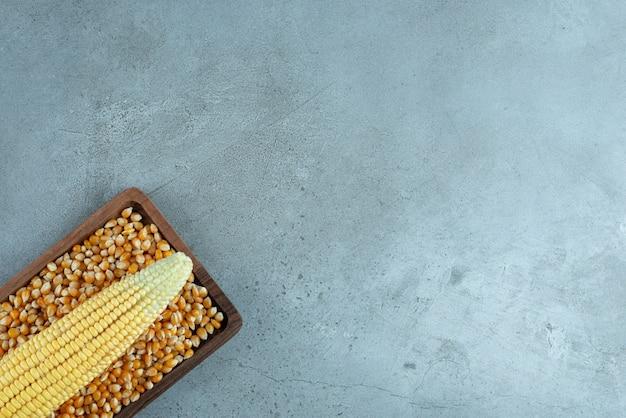 Eine maispflanze auf den samen auf einer holzplatte. foto in hoher qualität