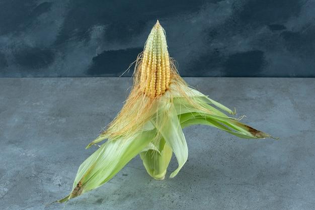 Eine maispflanze, die mit grünen blättern auf dem boden bedeckt ist. foto in hoher qualität