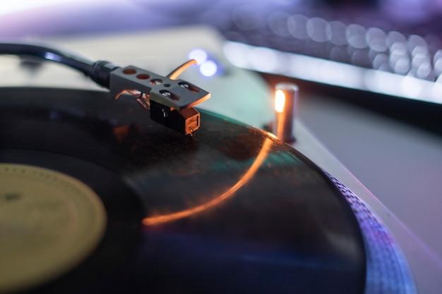 Eine makro-nahaufnahme der plattenspielernadel, die den altmodischen retro-musikplayer der vinylscheibe spielt