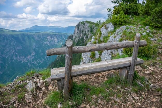 Eine malerische holzbank auf einer bergschlucht.