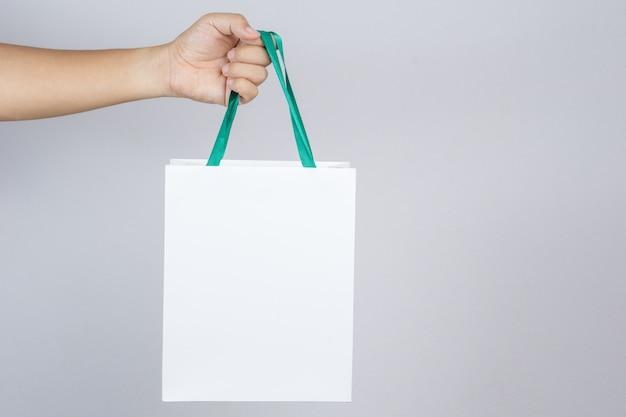 Eine mannhand, die einkaufstasche hält