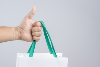 Eine Mannhand, die Einkaufstasche mit dem Daumen herauf Geste hält