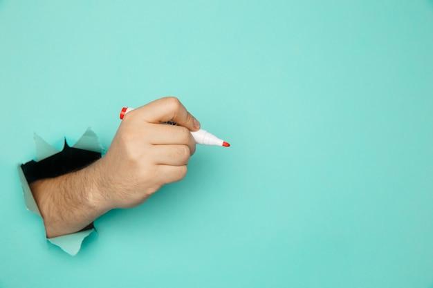 Eine mannhand mit marker durch eine zerbrochene blaue papierwand