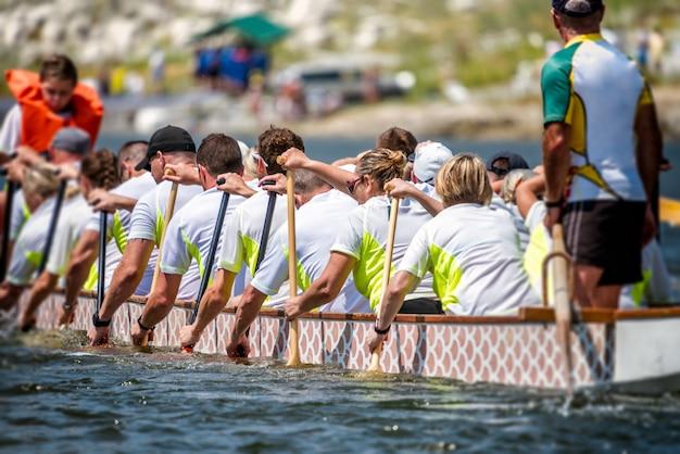 Eine mannschaft der drachenboot-rennläufer, die ihr boot paddeln