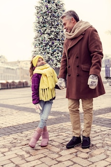 Eine mannschaft. hübscher mann, der hand seines kindes beim gehen nahe weihnachtsbaum hält