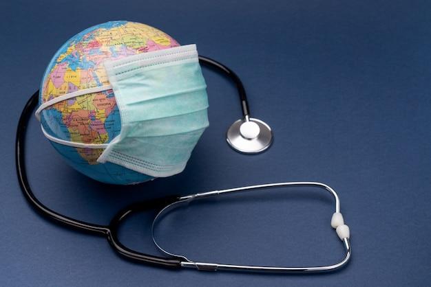 Eine medizinische coronavirus-maske mit einem stethoskop wird auf den globus gelegt. europäische union. europa.
