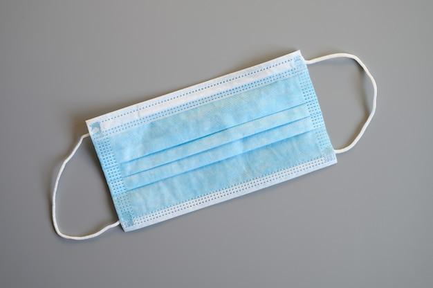 Eine medizinische einwegschutzmaske in blauer farbe mit ohrschlaufe zum abdecken von mund und nase zum schutz vor bakterien auf grauem hintergrund
