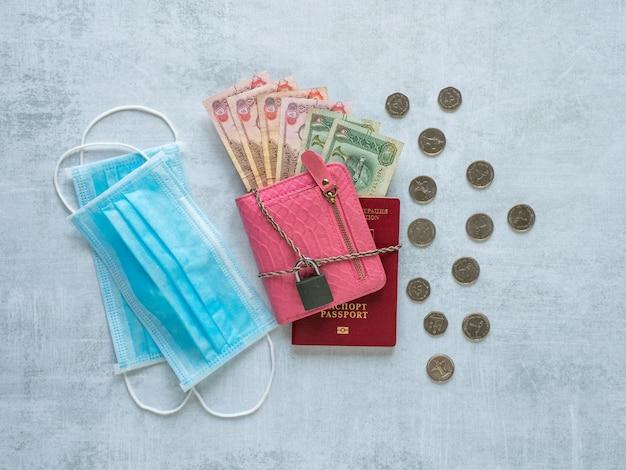 Eine medizinische maske, eine rosa brieftasche, arabische dirham, eine kette und ein schloss. pandemie und die wirtschaftskrise des konzepts