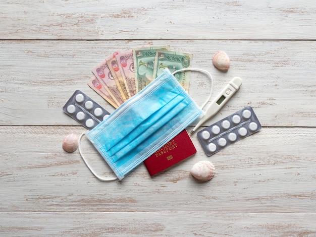 Eine medizinische maske, pillen, ein reisepass und geld liegen auf dem tisch. reisekonzept