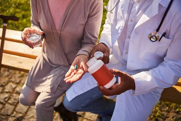 Eine medizinische person schüttelt einer rentnerpalme ein medikament aus einer flasche aus