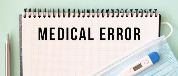 Eine medizinische schutzmaske und ein thermometer befinden sich auf dem notizblock. medical error text in einem notizbuch. medizinisches konzept.