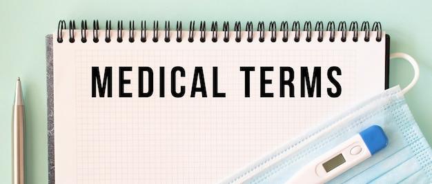 Eine medizinische schutzmaske und ein thermometer befinden sich auf dem notizblock. medizinische begriffe text in einem notizbuch. medizinisches konzept.