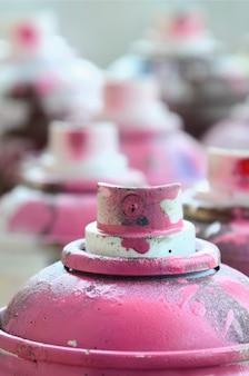 Eine menge schmutziger und gebrauchter aerosoldosen von hellrosa farbe