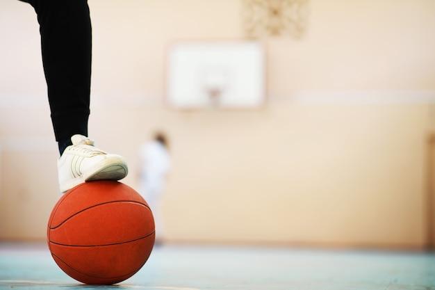 Eine menschliche fußstütze auf dem basketball auf betonboden. foto von einem basketball und turnschuhen in einem holzboden.
