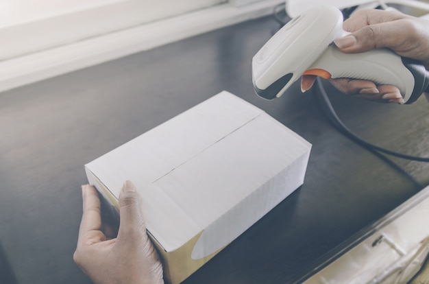 Eine menschliche hand, die paket mit barcodeleser für anlieferung hält.