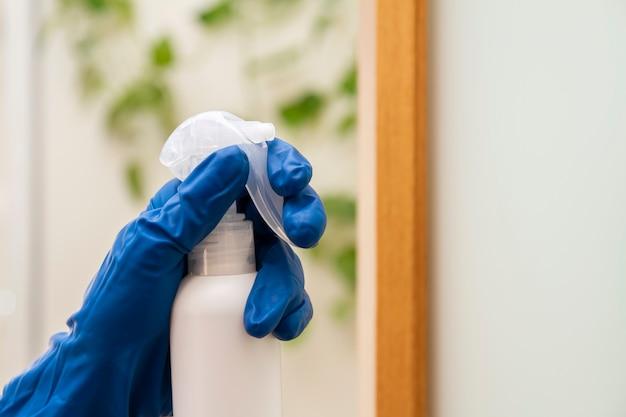 Eine menschliche hand in einem schutzhandschuh desinfiziert die oberfläche zur vorbeugung von viren